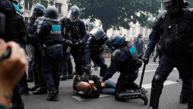 Policemen clash with a man in a demonstration part of a national day of protest against French legislation on compulsory Covid-19 health pass in Paris on July 31, 2021.