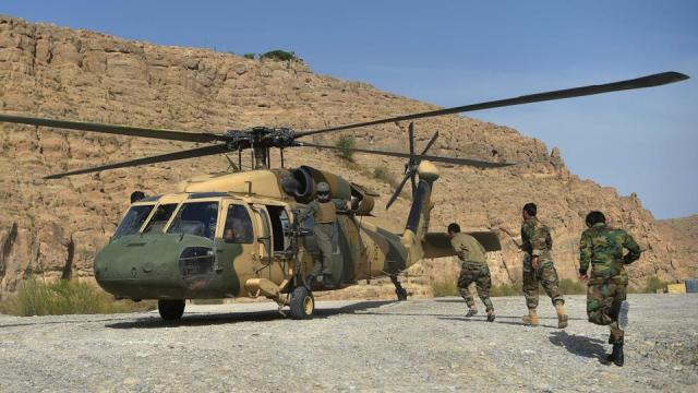 In this file photo taken on March 25, 2021 Afghan National Army (ANA) soldiers unload an Afghan Air Force Black Hawk helicopter at the hydroelectric Kajaki Dam in Kajaki, northeast of Helmand province.