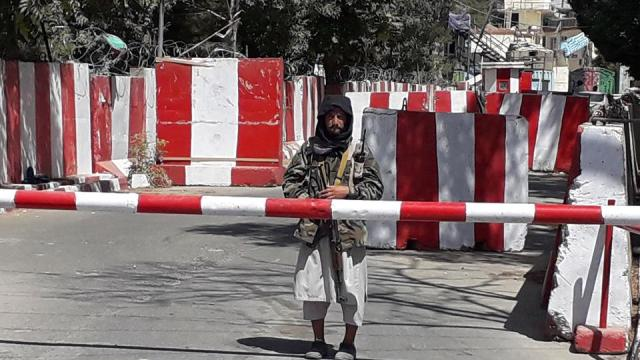 A Taliban militant stands guard at the entrance of the police headquarters in Ghazni on August 12, 2021, as Taliban move closer to Afghan capital after taking Ghazni city.