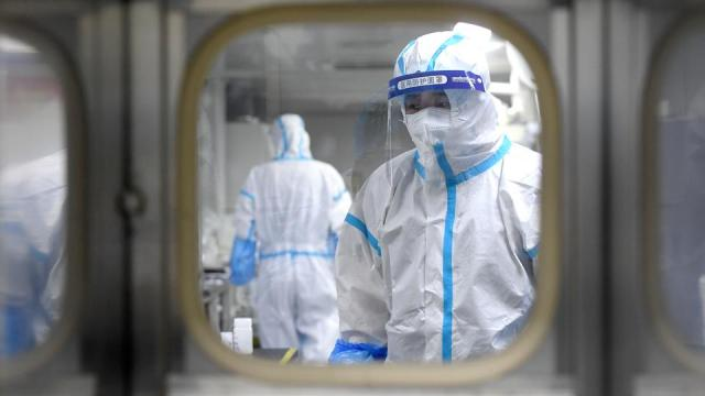 Medical workers in protective suits test nucleic acid samples inside a Huo-Yan (Fire Eye) laboratory of BGI, following new cases of the coronavirus disease in Wuhan, Hubei province, China, August 5, 2021.