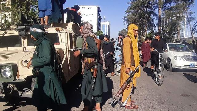 Taliban militants stand guard on August 13, 2021 along the roadside in Herat, Afghanistan's third biggest city, after govt forces pulled out the day before following weeks of being attacked.