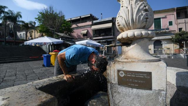 A man refreshes himself at a fountain in Aci Trezza, near Catania, Sicily, Italy, August 13, 2021.