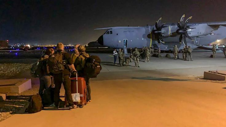 French and Afghan nationals wait to board a French military transport plane at the airport in Kabul on August 17, 2021.