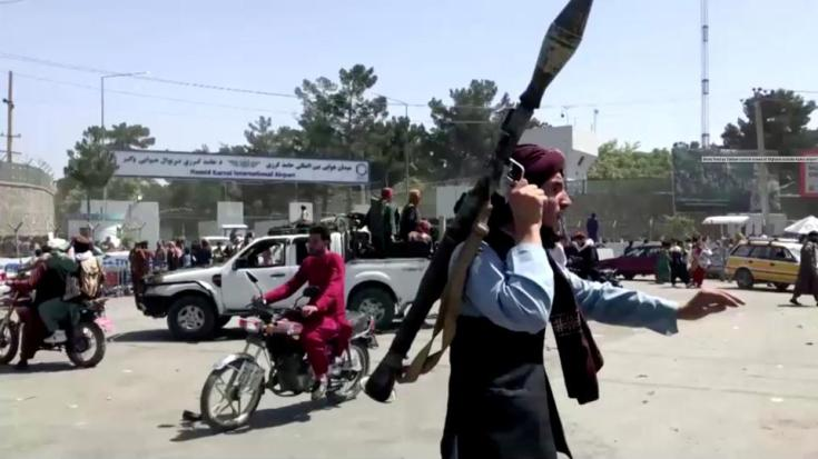 A Taliban fighter runs towards crowd outside Kabul airport, Kabul, Afghanistan August 16, 2021, in this still image taken from a video.