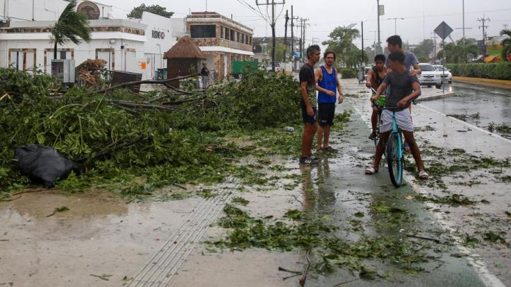 People gather near downed trees after Hurricane Grace made landfall on the Yucatan Peninsula, in Tulum, Mexico, August 19, 2021.
