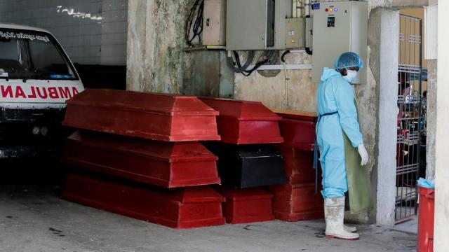 A medical official stands next to coffins for bodies of coronavirus disease victims at Judicial Medical Officer's premises in Colombo, Sri Lanka on August 20, 2021.