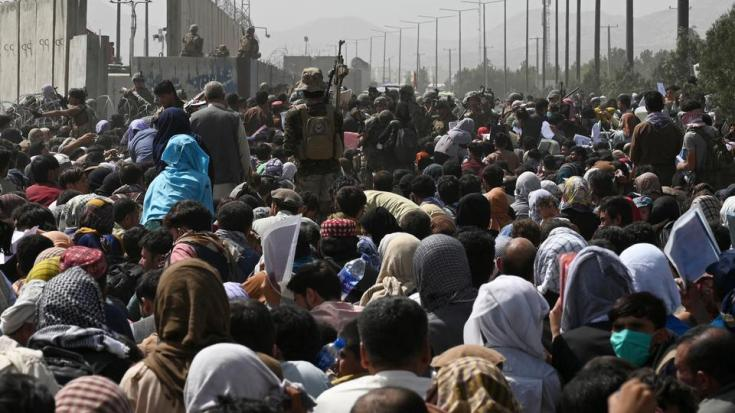 Afghans gather on a roadside near the military part of the airport in Kabul, hoping to flee from the country after the Taliban's military takeover of Afghanistan on August 20, 2021.