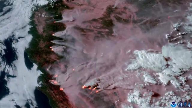 This still image taken from a video by the National Oceanic and Atmospheric Administration's GOESWest satellite, shows smoke rising from numerous wildfires in California on August 16, 2021.