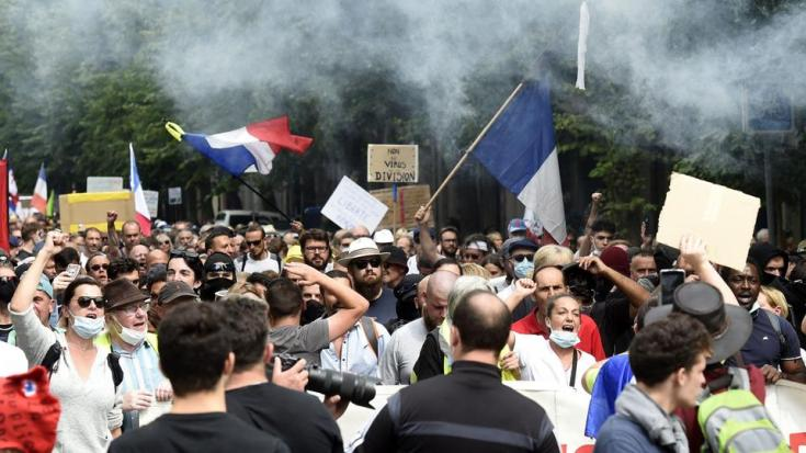 Protesters shout and wave flags during a protest against compulsory use of health pass called for by the French government, in Lille, northern France, on August 21, 2021.