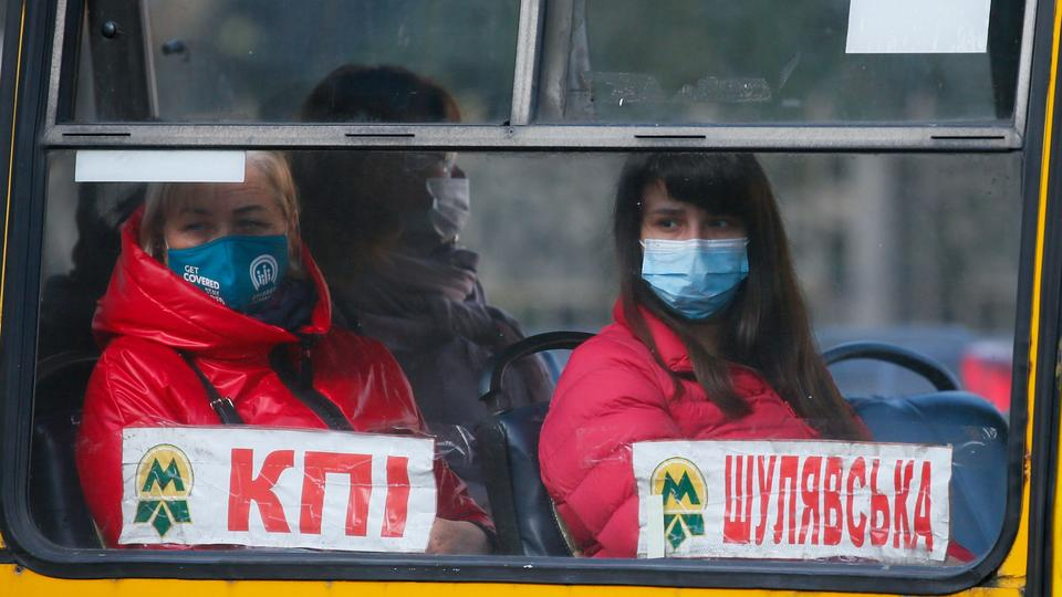 People wear protective face masks sit in a bus amid the ongoing coronavirus outbreak in central Kiev, Ukraine on September 29, 2021.