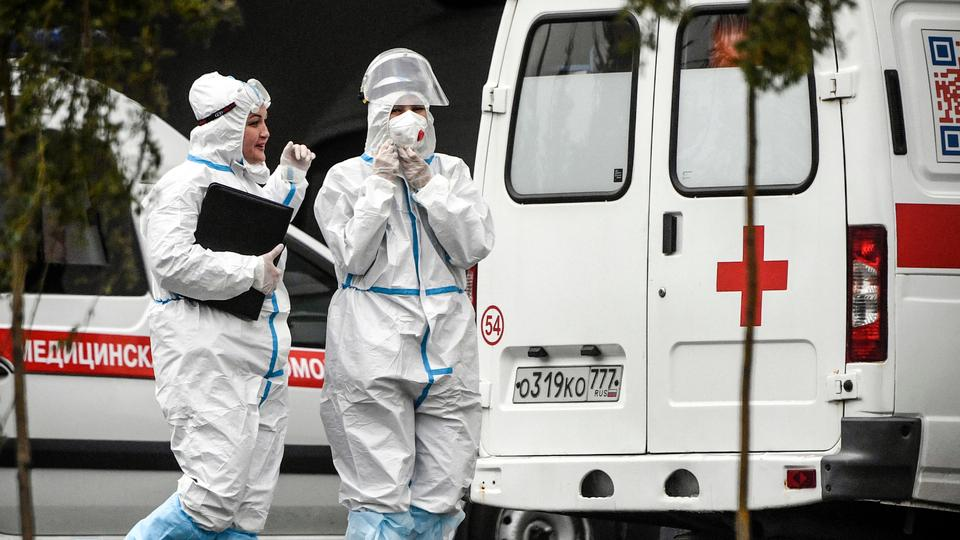 Medical staff members walk past ambulances at a hospital for the Covid-19 infected patients at Kommunarka outside Moscow, on 5 October 2021.