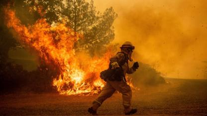 A firefighter runs while trying to save a home as a wildfire tears through Lakeport, Calif.ornia. July 31, 2018.