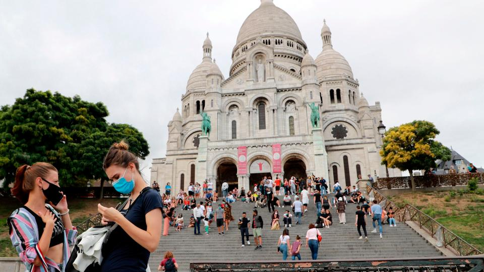 People wearing face masks stand in front of le Sacre Coeur in Paris, France on August 27, 2020.