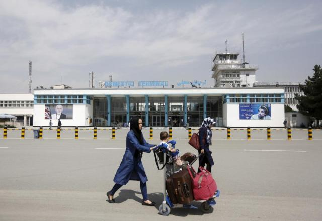 Afghan passengers walk in front of Hamid Karzai International Airport in Kabul, Afghanistan March 29, 2016.