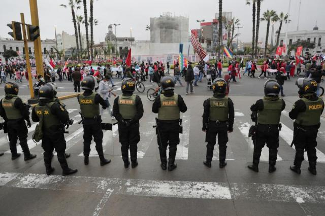 Supporters of Peru's presidential candidate Pedro Castillo gather as police officers stand guard in Lima, Peru on June 19, 2021.