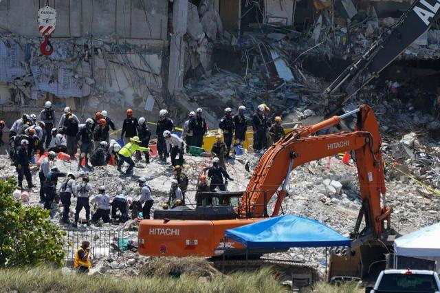 Search and rescue personnel work atop the rubble at the Champlain Towers South condo building, where scores of victims remain missing more than a week after it partially collapsed, July 2, 2021, in Surfside, Fla.