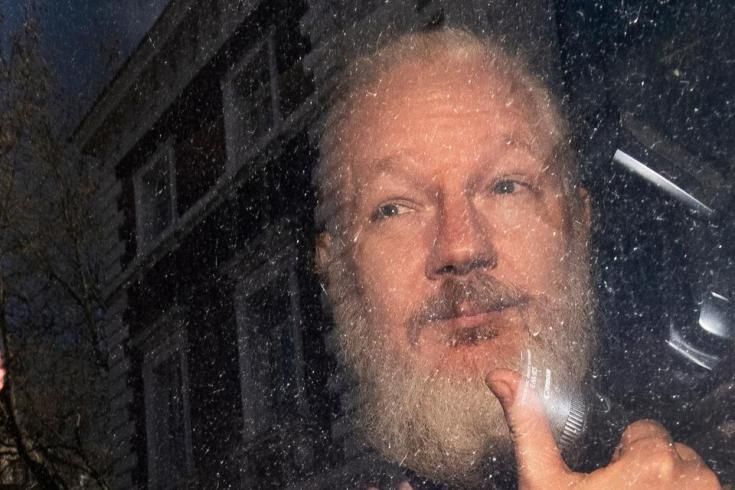 Assange gestures as he arrives at Westminster Magistrates' Court in London, after he was arrested by Metropolitan Police at the Ecuadorean embassy after his asylum request was rejected, on April 11, 2019. He was taken into custody for failing to surrender to the court in 2012, and has remained imprisoned at London's Belmarsh facility since.