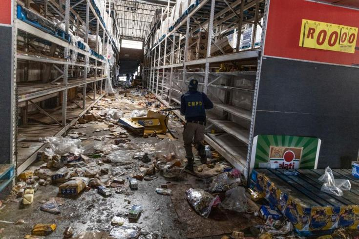 A member of the South African Police Services (SAPS) searches for looters inside the Gold Spot Shopping Centre in Vosloorus, southeast of Johannesburg, on July 12, 2021.