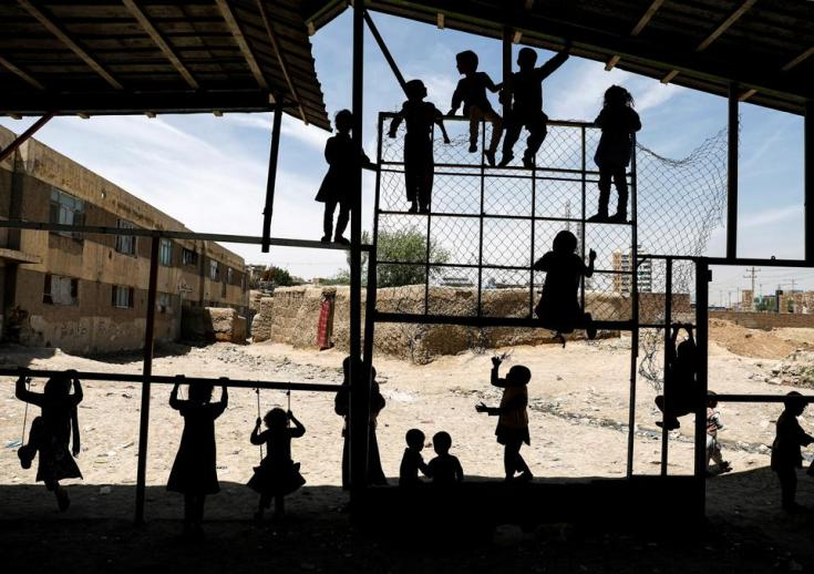 Internally displaced Afghan children play outside their shelter in Kabul on May 7, 2020.