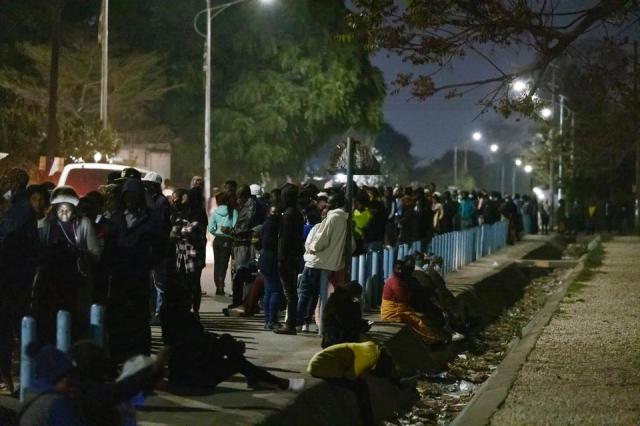 People queue as they wait for the opening of a polling station set up in the Matero secondary school in Lusaka on August 12, 2021.