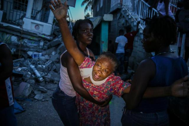 Oxiliene Morency cries out in grief after the body of her 7-year-old-daughter Esther Daniel was recovered from the rubble of their home destroyed by the earthquake in Les Cayes, Haiti, August. 14, 2021.