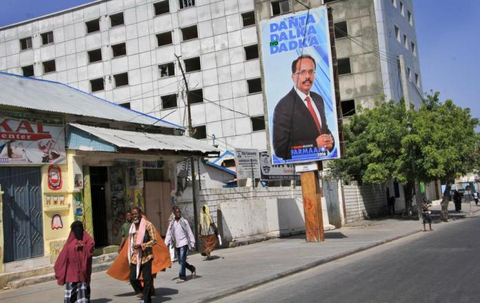 """Somalis walk past a campaign poster for candidate Mohamed Abdullahi """"Farmajo"""" Mohamed on the eve of presidential elections in Mogadishu, Somalia, Tuesday, February 7, 2017. The text reads """"the interest of the country and the people""""."""