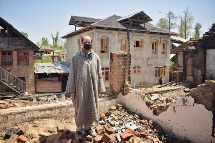 Altaf Wani, a cable operator, stands on the remains of his house in the Khudwani area of south Kashmir's Kulgam district, which was reduced to rubble by Indian soldiers during a gunfight with rebels in April this year.