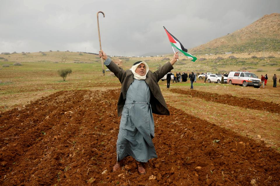 A demonstrator holds up a cane and a Palestinian flag during a protest against the US President Donald Trump's Middle East peace plan, in Jordan Valley in the Israeli-occupied West Bank January 29, 2020.