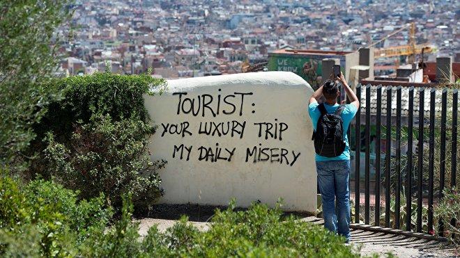 Vista a la ciudad de Barcelona desde el Park Guell, con una inscripción'Turista: tu viaje de lujo es mi miseria diaria'