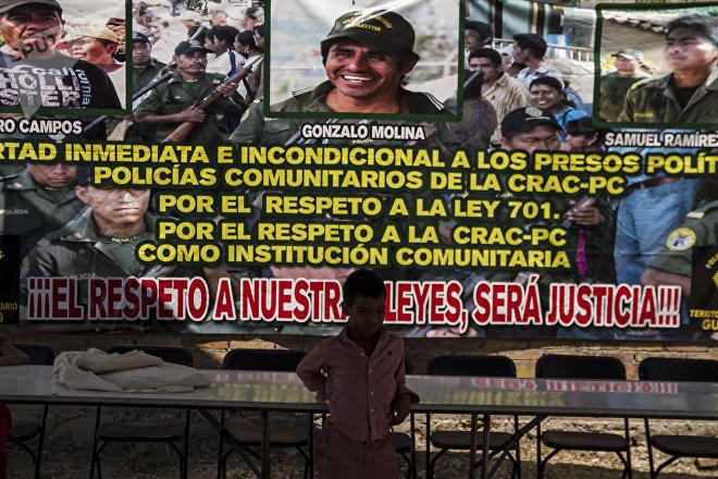 Guerrero. Niño corre frente una manta que exige la liberación de Gonzalo Molina.
