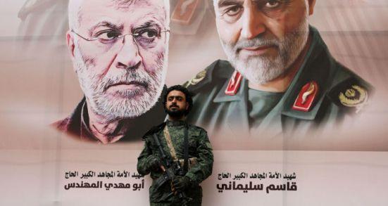 Un militar con el fondo del retrato del general Soleimani