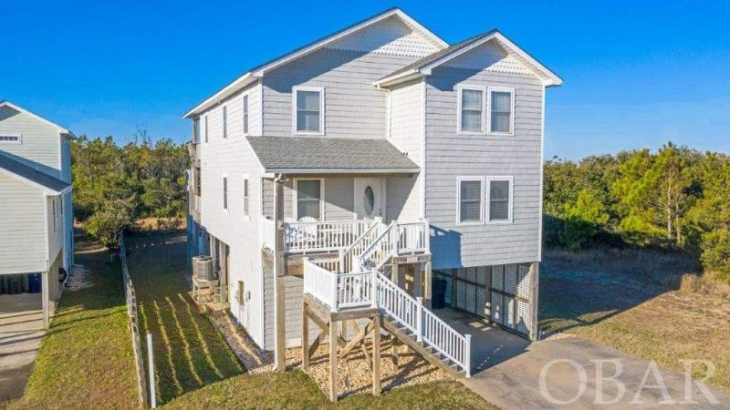 SEMI-OCEANFRONT IN S. Nags Head! Backs to Park Service privacy! This Custom Built Home is Beautiful Inside & Out *** NOTE: Tax Record states Built 2002 - but that is when the building permit was obtained... the Certificate of Occupancy per seller was issued Feb 2004 - that is the completion date and the true actual year built *** Home has never been rented & is in LIKE-NEW Condition! You will love the open Living Room area … marble foyer entry w/ red oak hardwood flooring * Custom Built Entertainment Center w/ Gas Fireplace (new in 2020!) - Note: Gas Fireplace is top of the line Gas Fireplace - per seller it does not have a pilot light and is operated by remote control so you never have to bend down to turn it on! * The Kitchen and dining area are fabulous … you might want to reconfigure the existing dining room into a sitting room or even an office as the Kitchen itself is approximately 35 feet long and has great table space * Kitchen features Door to Screened porch, Seamless Corian counters, all Custom Built Cabinets – you will love this space! * Three Bedrooms on the Top Level 3 – one is the Main Master Bedroom with a huge Sitting Room (the size of a bedroom itself and could function as a 5th Bedroom/Office/Sitting Room) with a large master bath and walk in closet * There is a private rear deck off the master bedroom overlooking the Park Service Land – check out  the OCEAN and SOUND Views from the rear deck * In the Deck Porch Roof there is a pull down stair in which there is plenty of room for storing screens, outside items, etc. * Level 2 Features Living, Dining, Eat-In Kitchen and 2 bedrooms – one of which is a second Master Bedroom … second level sun deck in the rear is also accessible here – which features a huge Screened Porch … decks are 10 feet wide for that extra room to enjoy price time or entertaining Friends & Family * The laundry washer & dryer are in a closet in the Kitchen * Interior stair down to the ground level Huge Storage Room/Workshop where y