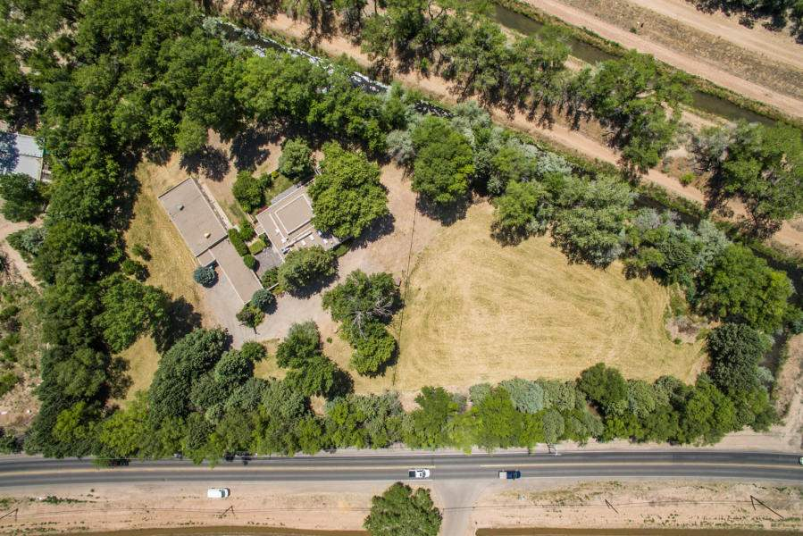 This gorgeous fully fenced, park-like property is located at the South End of Corrales Village on the east side of Corrales Road with easy access to Albuquerque & Rio Rancho. It has been subdivide into two lots. Lot 1 is 1.2115 ACRES. Lot 2 is 2.003 ACRES and has the Main home, Guest house, Car port, Workshop and Pump room located on it. The property can be purchased as one and subdivided later should the new owner wish to. All the paper work is complete and recorded. There is only one neighbor to the north, no others. This treed and meadowed property is surrounded on two sides by the Rio Grande and NMRGCD. Easy access to beautiful Bosque wooded hiking and biking trails and fishing and kayaking on the Rio Grande. Elementary is Corrales, Middle is Taylor, High School is Cibola.