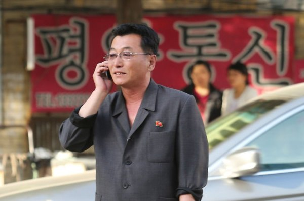 A North Korean man speak on his cell phone at the North Korean-China border. Smart phones and cell phones are increasingly becoming common, despite the restricted access that most users face due to state controls. Photo Credit: UPI