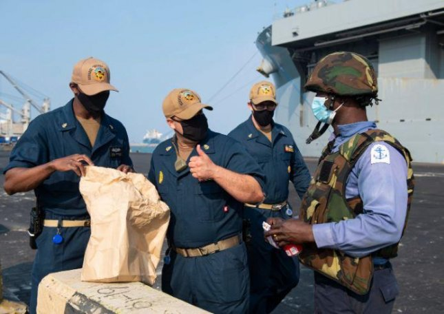A Nigerian Navy sailor, far right, meets crewmembers of the USS Hershel Woody Williams prior to exercises in the Gulf of Guinea. Photo by MCS3 Malachi Lekey/U.S. 6th Fleet