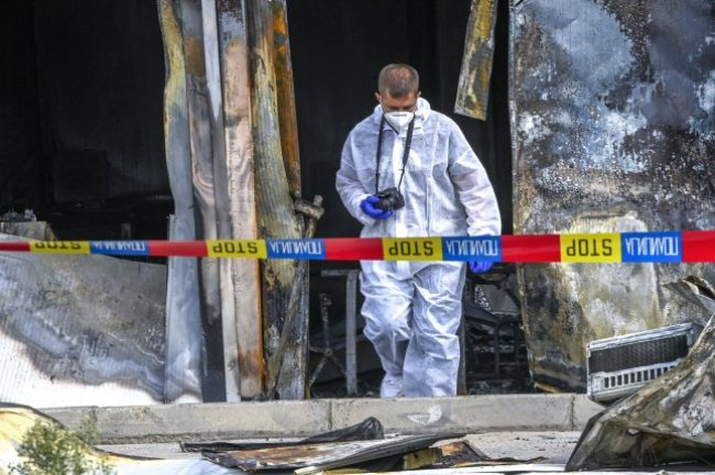 An investigator is seen Thursday at the site of a fire at a COVID-19 field hospital in Tetovo, North Macedonia. Officials said at least 14 people died in the fire. Photo by Georgi Licovski/EPA-EFE