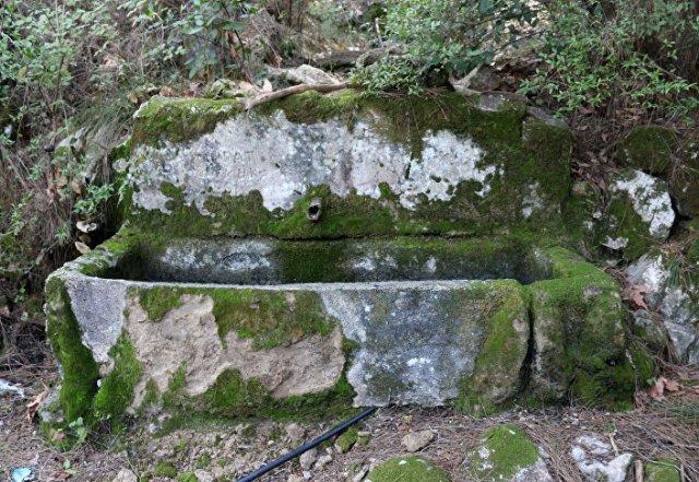 Oluğunun plastik oluşunun, yeterli yağış olduğunda, son zamanlara kadar çeşmenin kullanıldığını gösterdiğini anlatan Şaban Aktaş, Çeşme, son yıllarda kuraklık nedeniyle kurumuş görünüyor. Lahitlerin üstünde görüldüğü gibi, su akışından dolayı oluşan yüzlerce yıllık sarkıt oluşumları var, su akması için açılan gediklerden oluşan sarkıtlar. Dikkatle bakılırsa sol üstte çeşmenin adı da taşa kazınarak, yazılmış. Taşlar, yosun tuttuğu için tümüyle okunamıyor. Çeşme ormanlık alan içinde olması nedeniyle araçla ancak 7 kilometre yakınına kadar gidilebiliyor. Ulaşabilmek için antik kervan yolunda yaklaşık 3 saat yürümek gerekiyor dedi.
