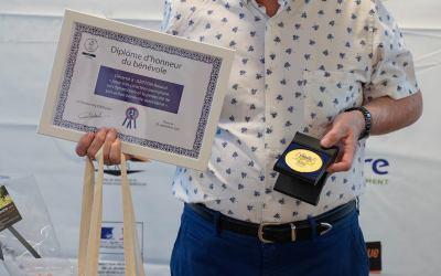 un bénévole avec sa médaille et son diplôme