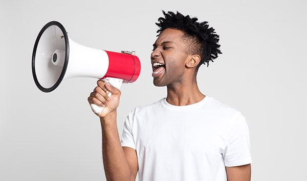 Man yelling share the care into a megaphone