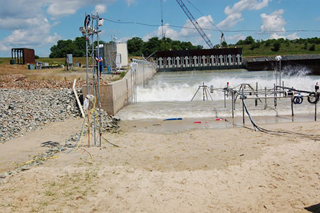 Large outdoor wave flume study of surrogate munition mobility and burial (blue and pink objects). Data were collected using imagers on towers and from sensors on the metal frames.