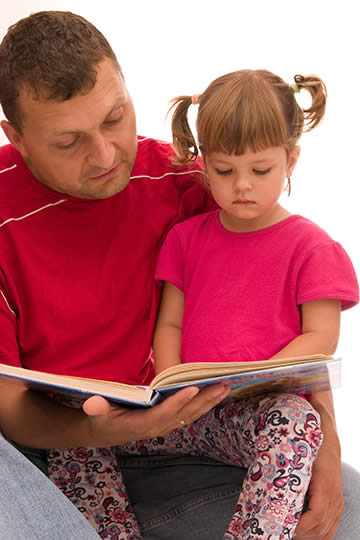 Child reading with her father