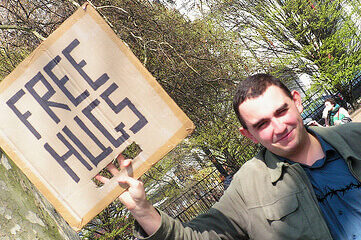 """photo of man holding sign that says """"FREE HUGS"""""""