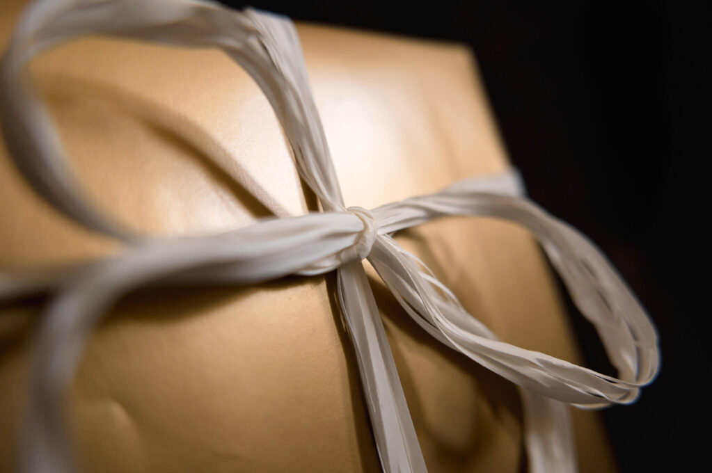 photo of a gold gift box with white bow