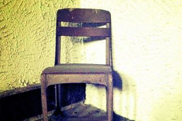 photo of old abndoned chair in room with yellow walls
