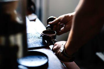 photo of barista tamping espresso
