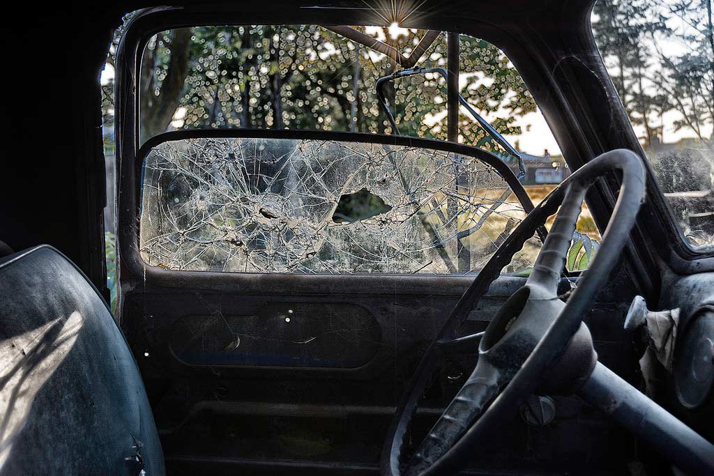 photo from inside of vehicle with a broken window next to steering wheel