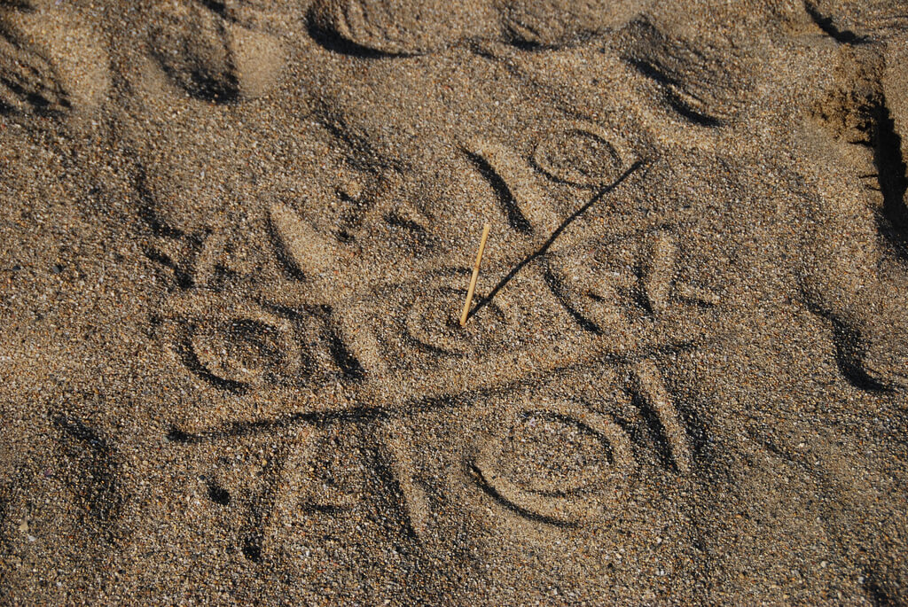 photo of tic-tac-toe game drawn into sand