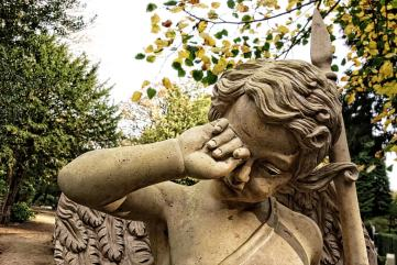 photo of angel statue rubbing its eye