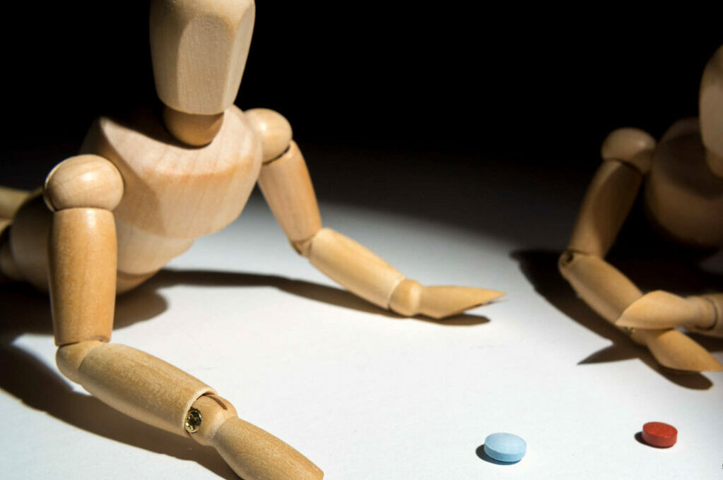 two artist mannequins looking at red and blue pills