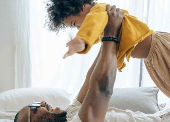excited black father and cute son having fun on bed